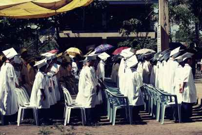 children wearing white academic gown during graduation ceremony at daytime
